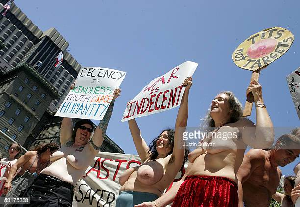 A group of women bare their breasts and hold signs against the war in Iraq in Union Square park June 30 2005 in San Francisco California A dozen men...
