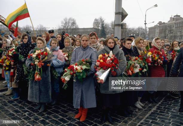 A group of women bring flowers to a funeral held for the victims killed in a demonstration against the Red Army's seizure of the television...