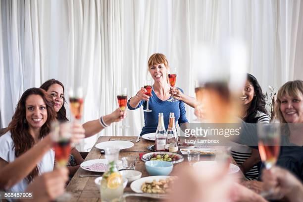 group of women bringing out a toast - mensch im hintergrund stock-fotos und bilder