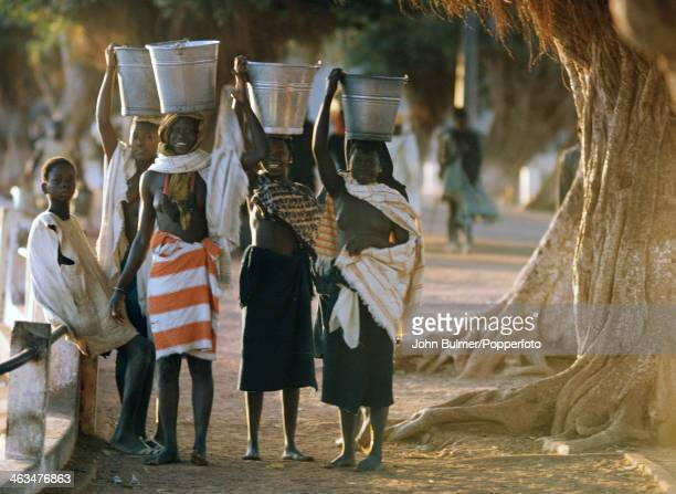 A group of women carry buckets of water on their heads in Mali in 1970
