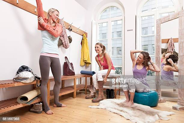 Group of women changing clothes in yoga studio changing room