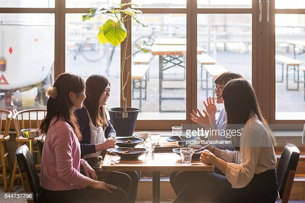Group of women chat while having meal.