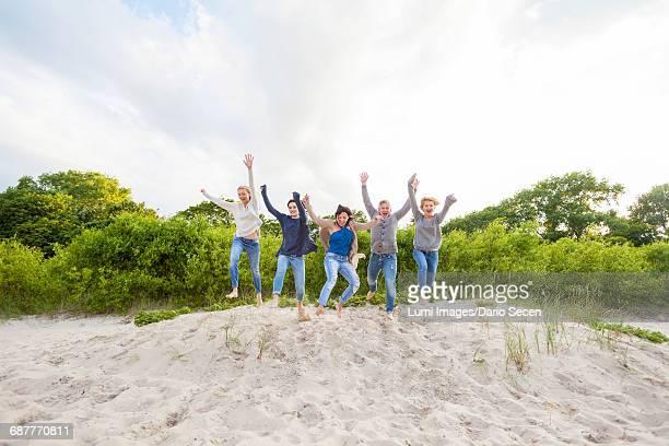 Group of women cheering on sandy beach