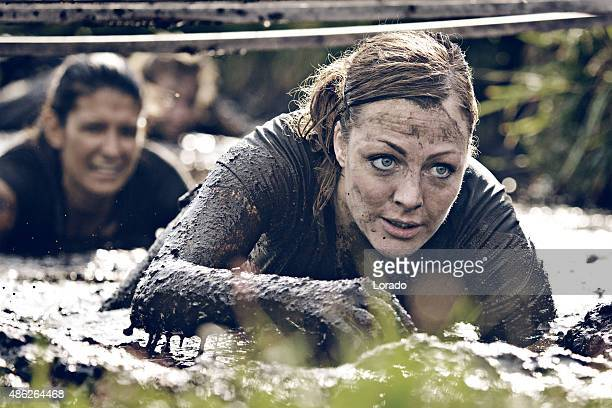 group of women crawling in mud - obstacle course stock photos and pictures