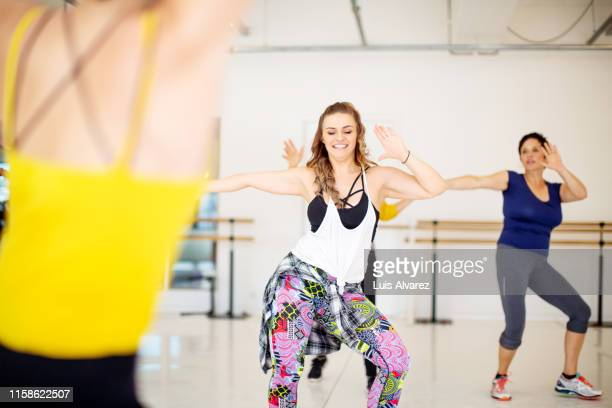 group of women dancing at health studio - active lifestyle stock pictures, royalty-free photos & images