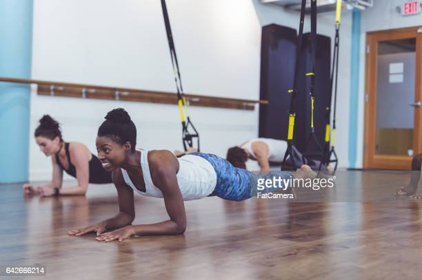 group of women doing barre + trx workout - barre class stock photos and pictures
