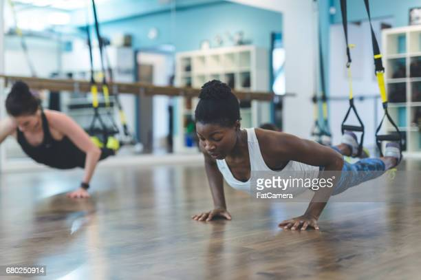 group of women doing trx workout - isometric projection stock photos and pictures