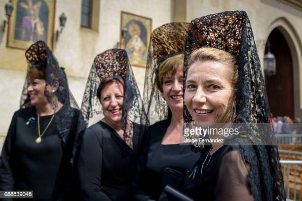 Group of women dressed in a very old fashion way with the traditional 'mantilla' and 'peineta' In Seville during what is known as 'Jueves Santo' or...