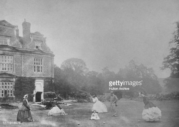 Group of women dressed in Victorian fashions, with bell-shaped skirts, playing croquet on the lawn, among them is a man in a grey suit, and a young...