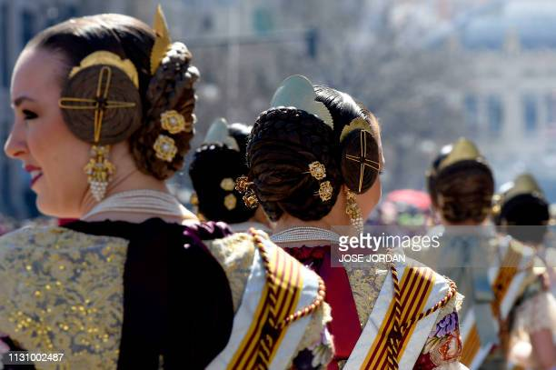 """Group of women dressed up in traditional """"fallera"""" costumes watch the 'Mascleta' during the Fallas festival in Valencia on March 16, 2019."""