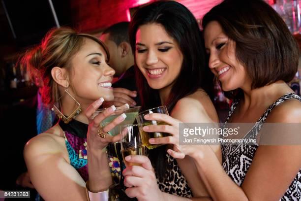 Group of women drinking cocktails nightclub