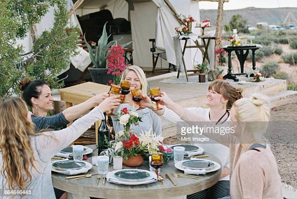 A group of women enjoying an outdoor meal by a large tent, in a desert landscape, raising a toast by clinking glasses.