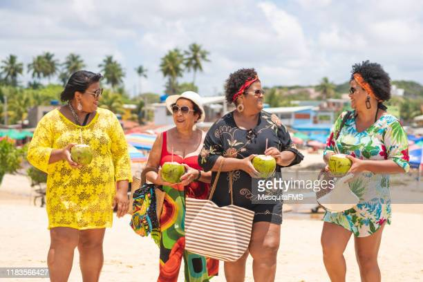 gruppe von frauen, die den tropischen strand genießen - dicke frauen am strand stock-fotos und bilder