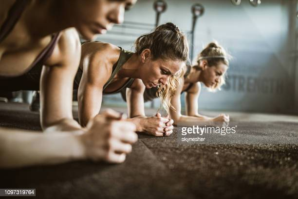 group of women exercising endurance in plank position at health club. - plank exercise stock pictures, royalty-free photos & images
