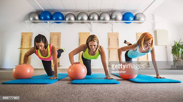 Group of women exercising with fitness balls in health club.