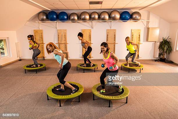 Group of women exercising with Pilates weights on trampolines.