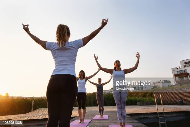 group of women exercising yoga on jetty in the city at sunrise