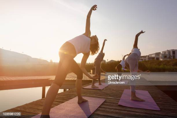 group of women exercising yoga on jetty in the city at sunrise - yoga stock pictures, royalty-free photos & images