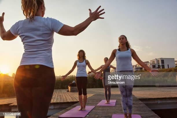 grupp kvinnor som utövar yoga på brygga i staden vid soluppgången - dortmund stad bildbanksfoton och bilder