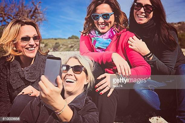Groupe de femmes amis faire la chasse aux selfies