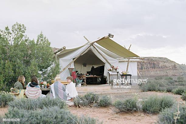 Group of women friends enjoying an outdoor meal in a desert by a large tent.