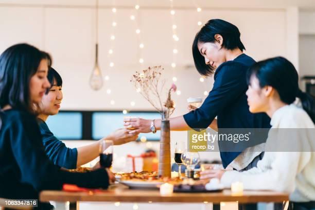 ホーム パーティーを楽しんでいる女性の友人のグループ - ディナーパーティー ストックフォトと画像