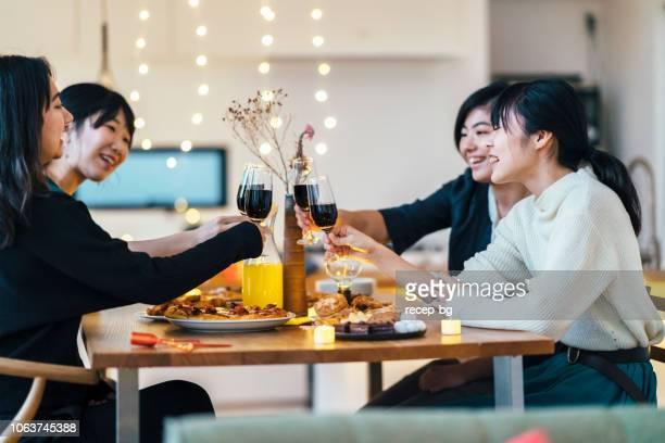ホーム パーティーを楽しんでいる女性の友人のグループ - 食卓 ストックフォトと画像