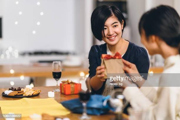 家で誕生日パーティーを持っている女性の友人のグループ - 贈り物 ストックフォトと画像