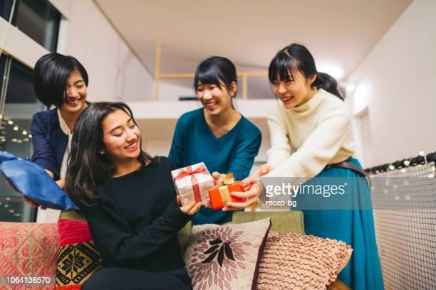 家で誕生日パーティーを持っている女性の友人のグループ - 誕生日の贈り物 ストックフォトと画像