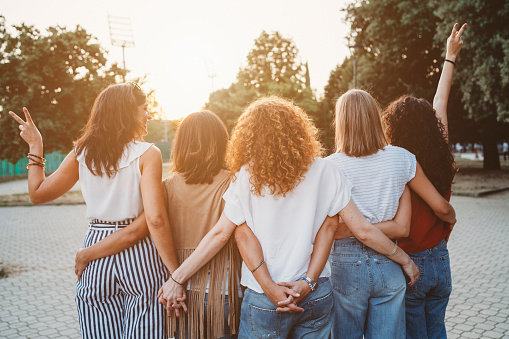Group of women friends holding hands together against sunset 1043062548