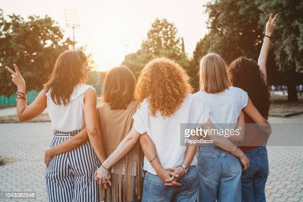 group of women friends holding hands together against sunset - gruppo di persone foto e immagini stock