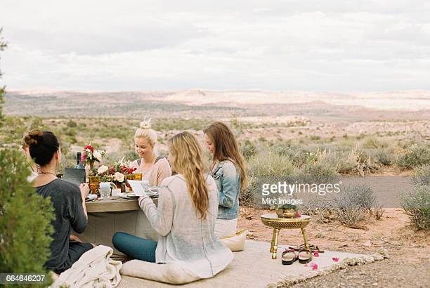 A group of women, friends sitting on the ground round a table having a meal.