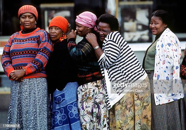 A group of women from Mdamstane Township giggle as they wait to vote in their country's first democratic election in East London South Africa 1994