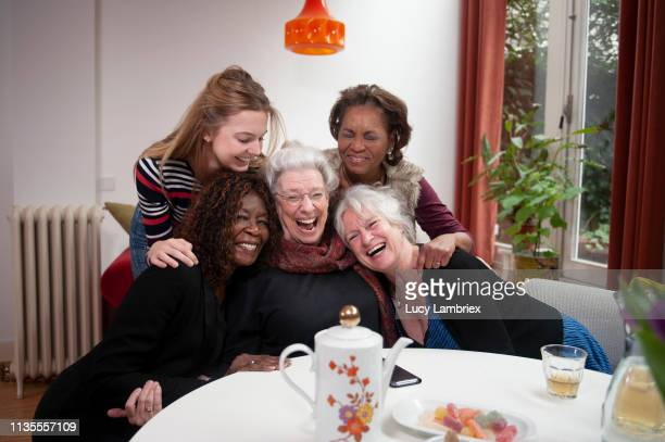 group of women gathered at a table, posing for a group photo - lucy lambriex stockfoto's en -beelden