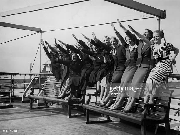 Group of women give the Nazi salute on the deck of the Wilhelm Gustloff at Tilbury, 10th April 1938. The ship is a floating polling station enabling...
