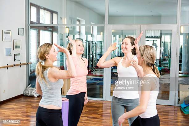 Group of women giving high-five to each other in gym