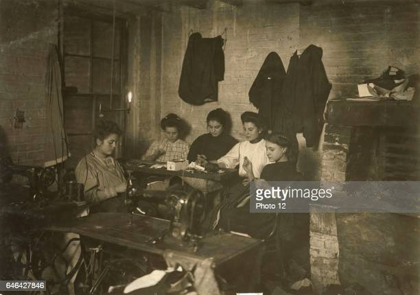 Group of women in a New York sweatshop making garments In the foreground are sewing machines The young girl by the fireplace is probably 14years old...