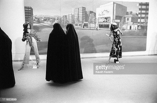 Group of women in black chador, view mannequins dressed in clothing styles popular prior to Iran's Islamic revolution of 1979, at the Tehran Museum...