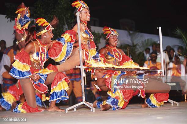 Group of women in carnival costumes doing limbo dance