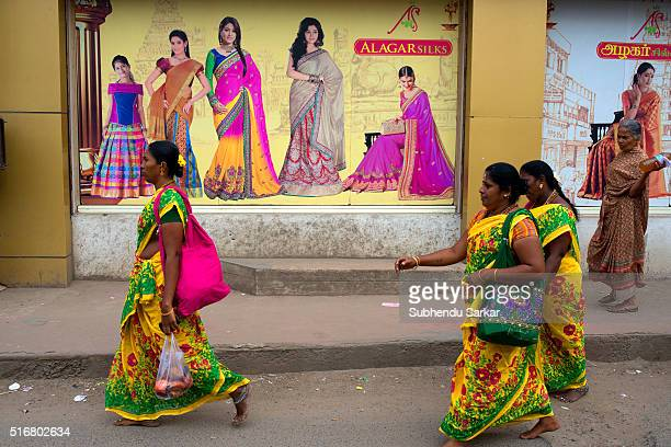 A group of women in colorful saris walk on a street in Madurai near Meenakshi temple