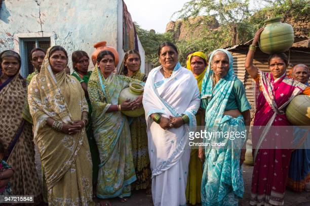 A group of women in colourful saris and bindis on their forehead are gathered in small village on March 28 2013 in Bijapur India A shack can be seen...