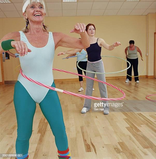 Group of women in gym studio, exercising using plastic hoops