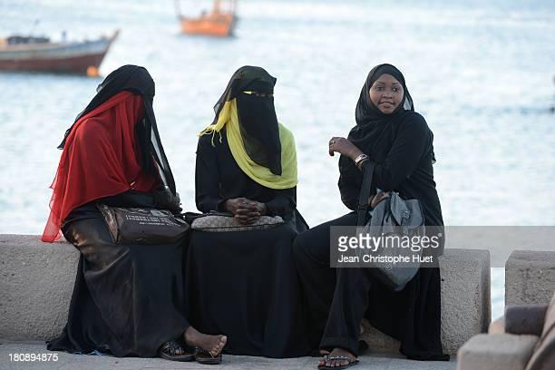 Group of women in hijab, on Zanzibar waterfront.