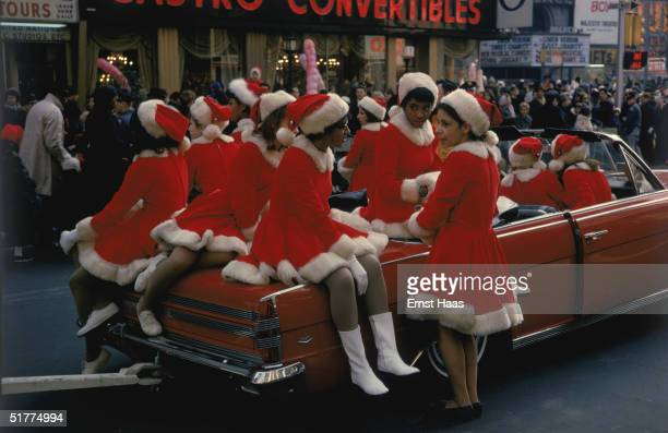A group of women in santa costumes ride through the streets of New York in a red convertible 1969