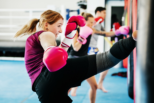 Group Of Women Kickboxing Together At Gym 970126044