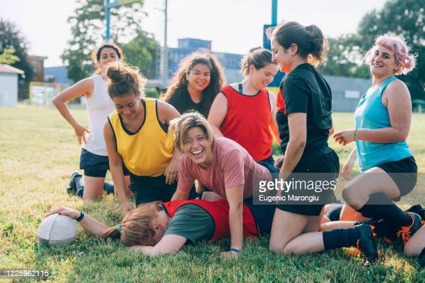 a group of women kneeling on a rugby pitch and laughing with one lying on the ground face down. - rugby team stock pictures, royalty-free photos & images