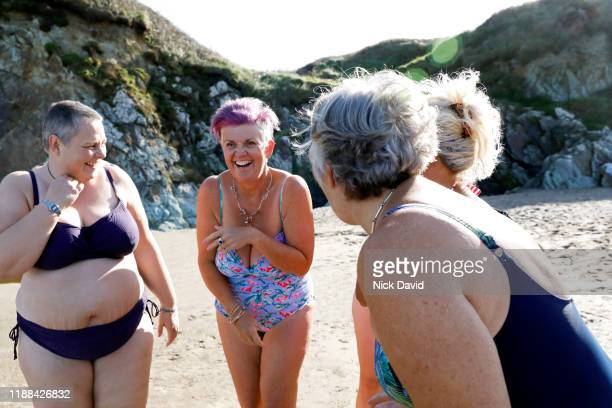 A group of women laughing and having fun together as they get ready for a swim in the sea.