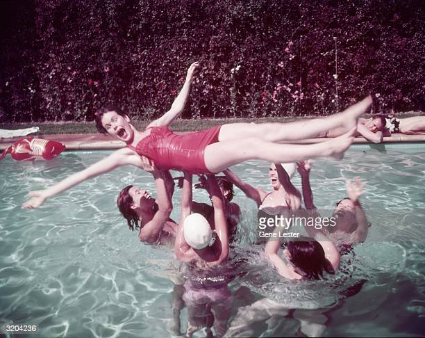 A group of women lift another woman wearing a red swimsuit out of the water during a swimming pool party at the home of American swimwear designer...