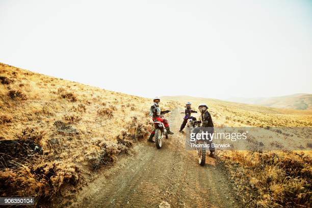 Group of women looking over shoulders while resting during dirt bike ride on desert road
