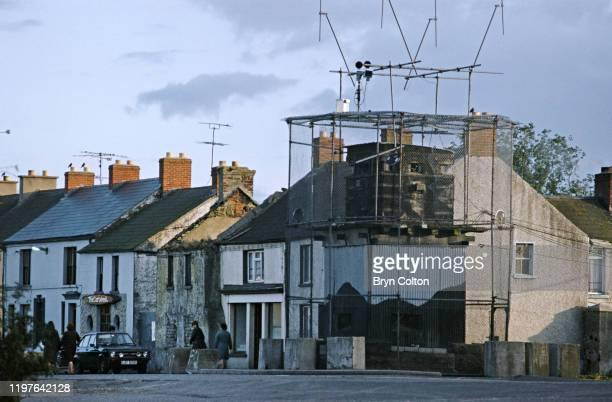 A group of women make their way past a fortified British army lookout post in the village square of Crossmaglen County Armagh Northern Ireland in...